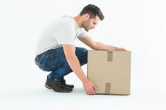 Delivery man crouching while picking cardboard box Stock Image