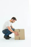 Delivery man crouching while picking cardboard box. Full length side view of delivery man crouching while picking cardboard box on white background Royalty Free Stock Images