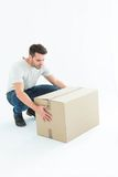 Delivery man crouching while picking cardboard box. Full length of delivery man crouching while picking cardboard box on white background Stock Images