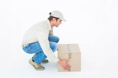 Delivery man crouching while picking cardboard box Stock Photography