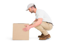 Delivery man crouching while picking cardboard box Royalty Free Stock Images