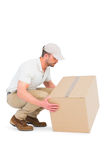 Delivery man crouching while picking cardboard box. On white background Royalty Free Stock Photography