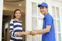 Delivery man and customer holding pizza royalty free stock photo