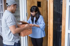 Delivery man delivering box. Smiling delivery men holding a cardboard box while beautiful women putting signature in clipboard Royalty Free Stock Photography