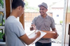 Delivery man delivering box. Smiling delivery men holding a cardboard box while handsome men putting signature in clipboard Royalty Free Stock Photo