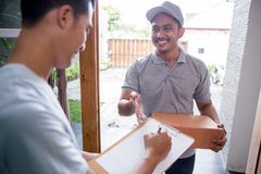 Delivery man delivering box. Smiling delivery men holding a cardboard box while handsome men putting signature in clipboard Stock Image