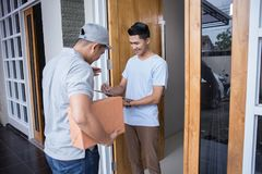 Delivery man delivering box. Smiling delivery men holding a cardboard box while handsome men putting signature in clipboard Royalty Free Stock Photography