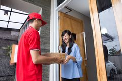 Delivery man delivering box. Smiling delivery men in red uniform delivering parcel box to recipient Stock Photography