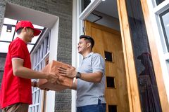 Delivery man delivering box. Smiling delivery men in red uniform delivering parcel box to recipient Royalty Free Stock Photography