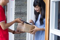 Delivery man delivering box. Smiling delivery men in red uniform delivering parcel box to recipient Stock Image