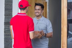 Delivery man delivering box. Smiling delivery men in red uniform delivering parcel box to recipient Royalty Free Stock Photos