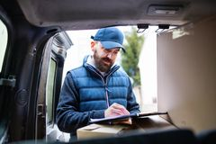 Delivery man delivering parcel box to recipient. royalty free stock image