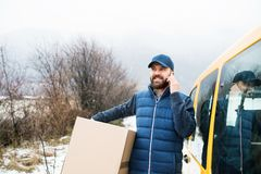 Delivery man delivering parcel box to recipient. Delivery man delivering parcel box to recipient - courier service concept. A man with a smartphone making a stock photo