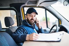 Delivery man delivering parcel box to recipient. Delivery man delivering parcel box to recipient - courier service concept. A man with a smartphone making a Stock Images