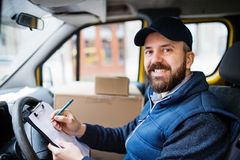 Delivery man delivering parcel box to recipient. stock image