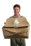 Delivery Man In Denial. A delivery man holding a smashed package and trying to smile like there's nothing wrong. (focus on his face royalty free stock image