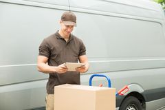 Delivery Man With Digital Tablet And Boxes. Young Happy Delivery Man With Digital Tablet And Cardboard Boxes Royalty Free Stock Photo