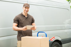 Delivery Man With Digital Tablet And Boxes. Young Happy Delivery Man With Digital Tablet And Cardboard Boxes Royalty Free Stock Photos