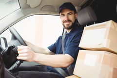 Delivery man driving his van. With packages on the front seat Stock Photo