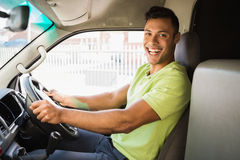 Delivery man driving his van while smiling at camera Royalty Free Stock Images
