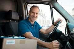 Delivery man driving van. With packages on the front seat. Happy mature courier in truck. Portrait of confident express courier driving his delivery van Stock Photos
