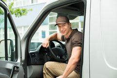 Delivery Man Driving Van. Young Happy Delivery Man Driving Service Delivery Van Stock Image