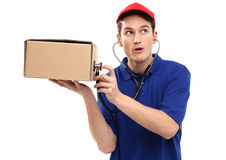 Delivery man examining box with stethoscope Stock Images