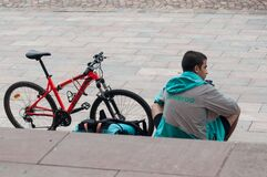 Free Delivery Man From Deliveroo British Company  In Mountain Bike Waiting For  Delivery To Be Made Sitting On Stairs In Outdoor Stock Photography - 175475782