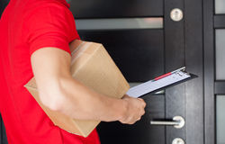 Delivery man at front door. Delivery guy waiting at front door with a parcel Royalty Free Stock Images