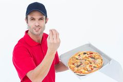 Delivery man gesturing while holding fresh pizza Stock Photos