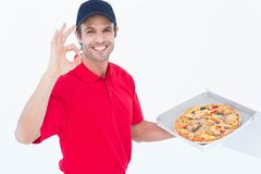 Delivery man gesturing okay while holding fresh pizza Stock Photo