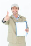 Delivery man gesturing thumbs up while showing clipboard Royalty Free Stock Photography