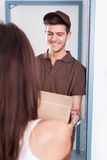Delivery man giving courier to woman Royalty Free Stock Image