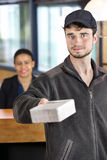 Delivery Man Giving Package In Office Royalty Free Stock Image