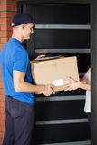 Delivery man giving parcel to homeowner Royalty Free Stock Photography