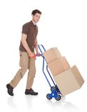 Delivery man with hand truck and boxes. Young Happy Delivery Man Carrying Boxes On A Hand Truck Stock Photography