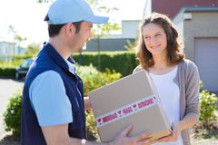 Delivery man handing over a parcel to customer Stock Image