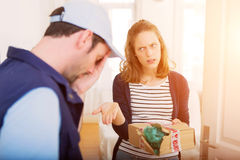 Delivery man handing over a parcel to customer Stock Photos
