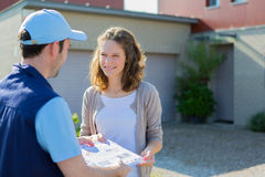 Delivery man handing over a registered letter Stock Image