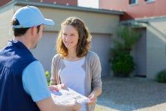 Delivery man handing over a registered letter Stock Image