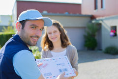 Delivery man handing over a registered letter Stock Photos