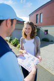 Delivery man handing over a registered letter Stock Images