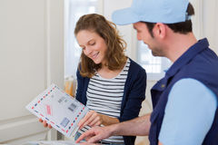 Delivery man handing over a registered mail royalty free stock photography