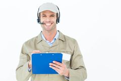 Delivery man in headphones holding clipboard Royalty Free Stock Photos
