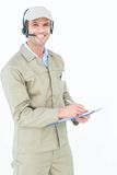 Delivery man in headphones writing on clipboard Stock Image