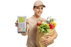 Delivery man holding a bag a groceries and a payment terminal. Isolated on white background Royalty Free Stock Images