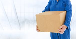 Delivery man holding a box against white background. Mid section of delivery man holding a box against white background Stock Images