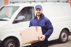 Delivery man holding box Stock Images