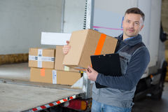 Delivery man holding box in front truck. Delivery man holding box in front of his truck stock images