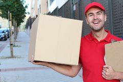 Delivery man holding a box outdoors stock images